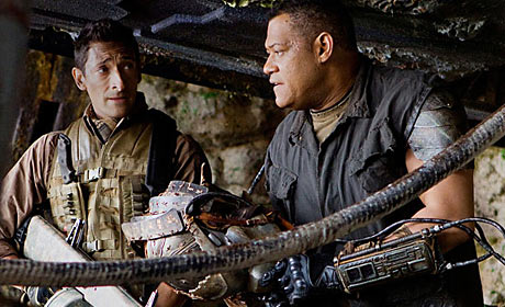 Noland (Laurence Fishburne, right) reveals to Royce (Adrien Brody) some of the secrets of living on an alien world - and amidst alien Predators. Photo:  Rico Torres