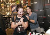 The Vampire Diaries star Michael Trevino signs a fan's t-shirt.